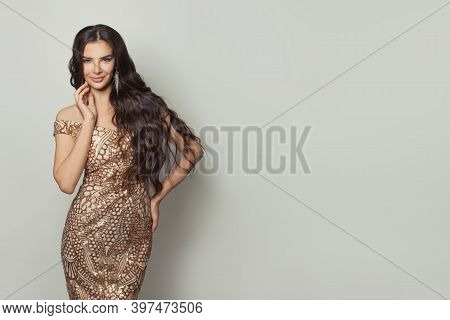 Cute Brunette Woman With Healthy Curly Hairstyle Wearing Gold Evening Gown Posing On White Backgroun