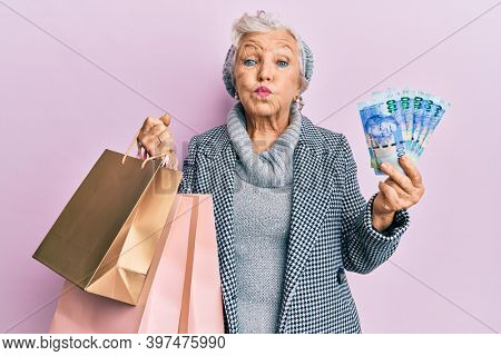 Senior grey-haired woman holding shopping bags and south africa rands banknotes puffing cheeks with funny face. mouth inflated with air, catching air.