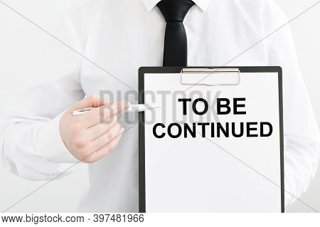 Card With Text To Be Continued In The Hands Of A Man On A Light Background
