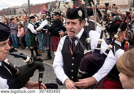 A Scottish Piper Plays A Traditional Bagpipe In The Street.