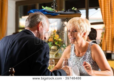 Pareja Senior fina cena comida en mesa en hotel o restaurante elegante