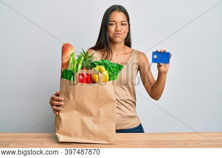 Beautiful hispanic woman holding groceries and credit card puffing cheeks with funny face. mouth inflated with air, catching air.