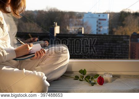 A Girl Sits On A Windowsill And Writes Something In A Notebook In The Morning