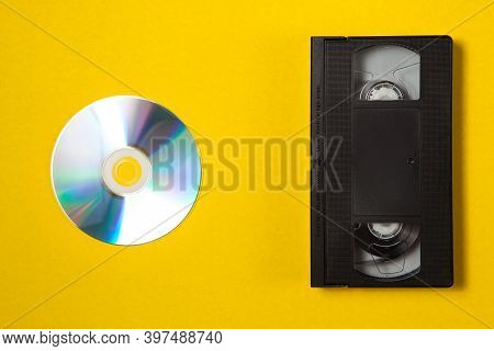 Video Cassette Videotape And Compact Disc On A Yellow Background. Flat Lay Concept.