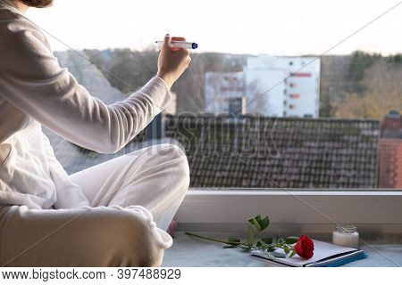 A Young Girl Sits On The Windowsill And Writes Something On The Window Glass