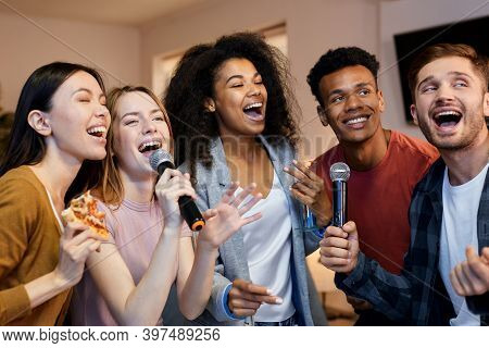 Sing It. Enthusiastic Group Of Friends Singing With Microphone While Playing Karaoke At Home, Standi