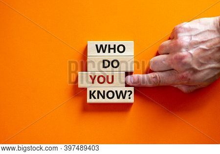 Who Do You Know Symbol. Wooden Blocks With Words 'who Do You Know'. Male Hand. Beautiful Orange Back