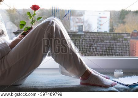 A Young Girl Is Bored In Quarantine On The Windowsill And Holds A Rose In Her Hand, In The Morning