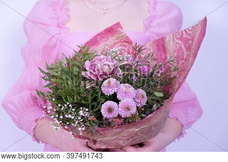 Girl In A Pink Dress Holding A Bouquet Of Festive Flowers On A White Background