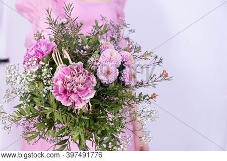 A Young Girl In A Pink Dress Holds A Bouquet Of Festive Flowers On A White Background
