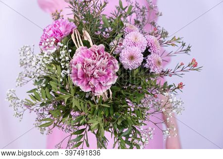 Young Girl In A Pink Dress Holding A Bouquet Of Festive Flowers On A White Background