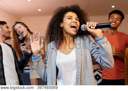 Sing On. Pretty Mixed Race Girl Looking Happy While Holding Microphone And Singing At Karaoke Party