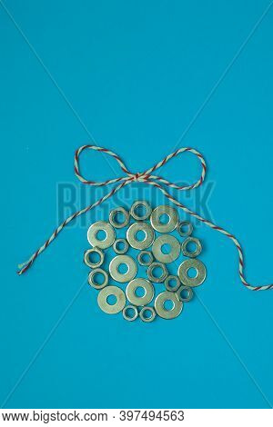 Christmas Ball From Washers And Nuts On Blue Paper. Metal Nuts. Washers And Grovers. Industrial New