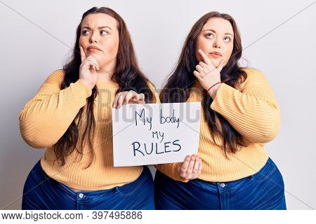 Young plus size twins holding my body my rules banner serious face thinking about question with hand on chin, thoughtful about confusing idea