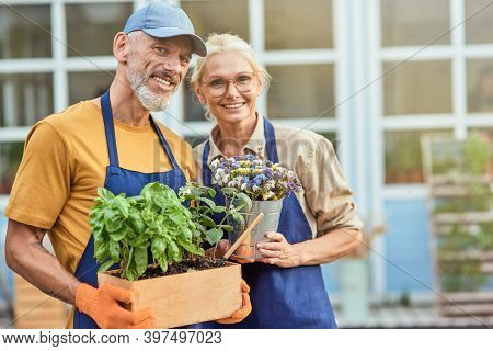 Middle Aged Spouses Smiling On Garden House Background