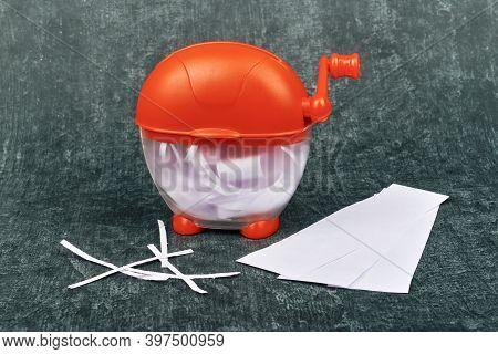 Paper Shredder Machine, Portable, Desktop, With Shredded Paper, Close-up On Gray Background