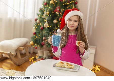 Beautiful Little Girl Wearing Santa Hat Sitting By Nicely Decorated Christmas Tree Having Breakfast,