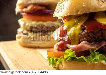 Two Hamburgers, Details Of Two Gourmet Double Burgers, Cheese, Tomato, Bacon, Lettuce, Onion. On Woo