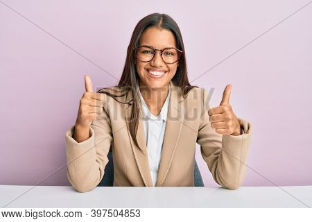 Beautiful hispanic woman working at the office success sign doing positive gesture with hand, thumbs up smiling and happy. cheerful expression and winner gesture.