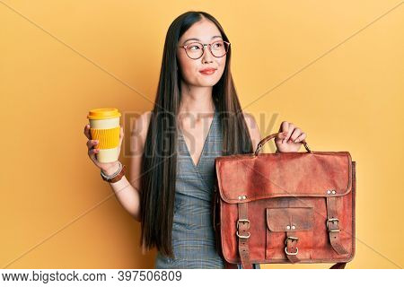 Young chinese woman holding leather bag and drinking a take away coffee smiling looking to the side and staring away thinking.