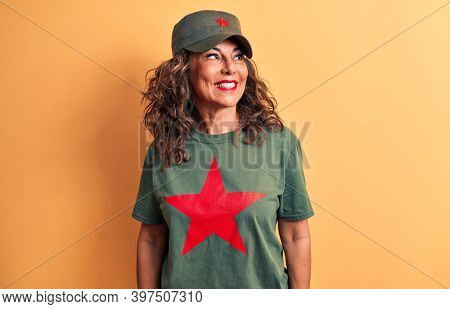 Middle age brunette woman wearing t-shirt and cap with red star symbol of communism looking to side, relax profile pose with natural face and confident smile.