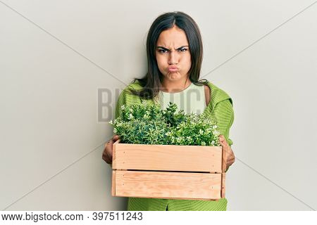 Young brunette woman holding wooden plant pot puffing cheeks with funny face. mouth inflated with air, catching air.