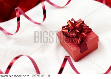 Christmas Card With A Red Gift Box And Serpentine On A White Background Knitted Sweater. Copy Space.
