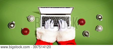 Santa Claus Using A Laptop Computer With Christmas Baubles From Above