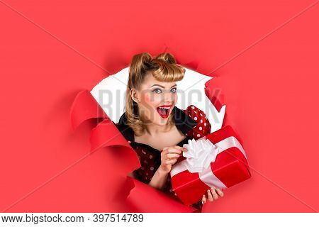Pin Up Girl With Gift. Breaking Paper. Surprised Retro Woman Hold Gift Box Through Hole In Paper. Wo