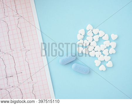 White Pills In Form Of Heart And Blue Tablets With Sign 500 On Blue Background With Electrocardiogra
