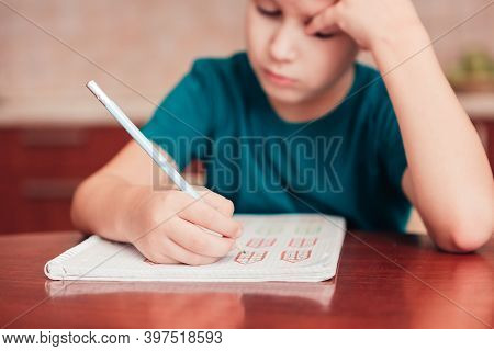 Close Up Of Schoolboy Learn Math At Homework, Small Dof, Focus On Hand With Pencil. Child Doing Deve