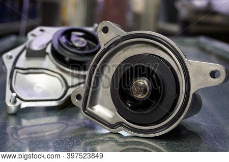 Close-up - Pump Of The Cooling System Of A Modern Car. In The Background Is Another Coolant Pump. Th