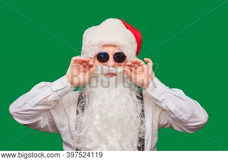 Winter Fashion And Sales. Portrait Of A Handsome Man In A Santa Hat, Winking While Standing Against