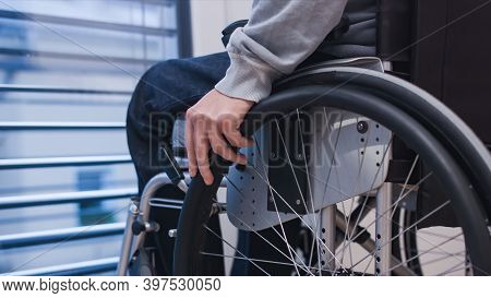Man On Wheelchair In Living Room Looking Through Window. Handicapped Invalid Paralysed Person, Depre