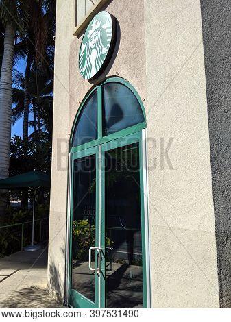 Waikiki - November 4, 2019: Starbucks Green Sign Above Door.  Starbucks Corporation Is An American C