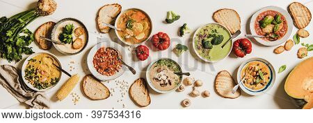Flat-lay Of Vegetarian Creamy Homemade Soup In Plates With Bread Slices Over White Plain Table Backg