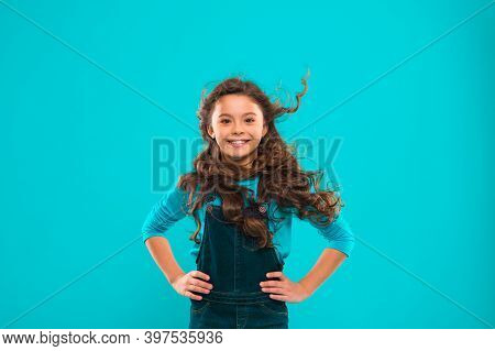 Little Girl With Long Hair. Kid Happy Cute Face With Adorable Curly Hair Stand Over Blue Background.