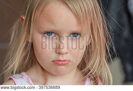 portrait of a five-year-old girl, blonde, sweet, pretty, offended, upset,