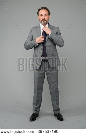 Making Great Impression. Mature Man Fix Tie Wearing Suit Grey Background. Professional Attire. Forma