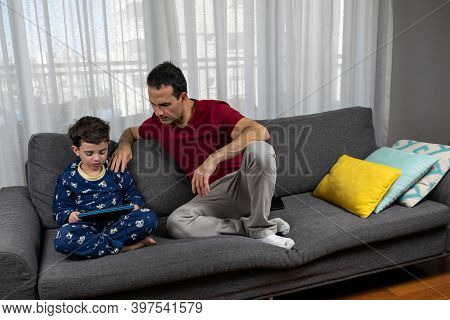Mature Man (44 Years Old) Sitting Next To His Son (6 Years Old) With His Hand On His Shoulder.