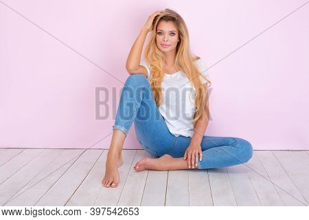 Beautiful Sexy Blonde Girl With Long Hair And Tanned Body Wearing White Shirt And Blue Jeans, Sittin