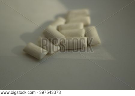 White Gum Pads Lie On A White Table. Chewing Gums To Eliminate Bad Breath. Mint Gum Pads.