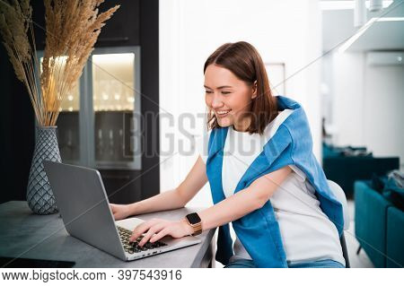 Smiling Woman Sitting In The Kitchen And Using The Laptop. Working From Home In Quarantine Lockdown.