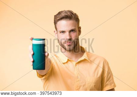 Man On Confident Face Recommends Shampoo, Yellow Background. Guy With Bristle Holds Bottle Of Shampo