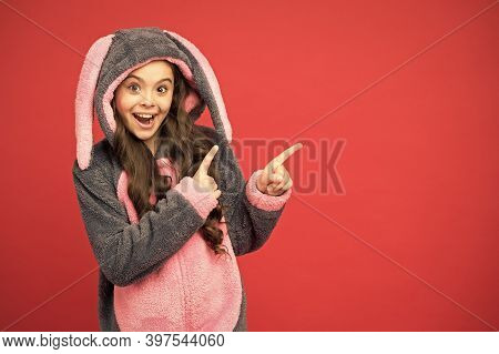 Take A Look. Happy Girl Pointing Index Fingers At Something. Small Child In Bunny Pajamas Pointing R