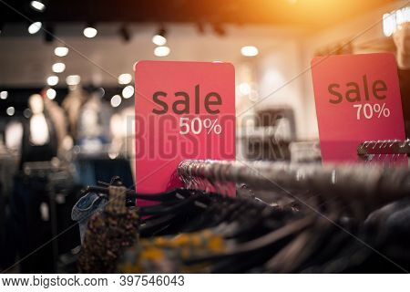 Sale Of Past Collections. Shopping In Store. Clothes On Hangers In Shop For Sale. Blur Background. F