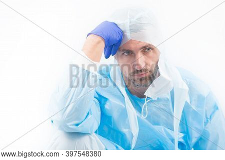 Tired Man Doctor Epidemiologist In Safety Protective Costume On Coronavirus Pandemic Quarantine Isol