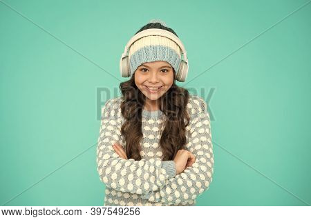 Happy Girl Enjoy Winter Playlist. Music Mood. Cheerful Little Child Knitted Sweater And Hat. Smiling
