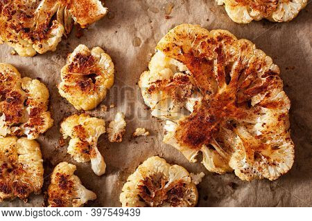 cauliflower steaks with herb and spice on baking tray. plant based meat substitute