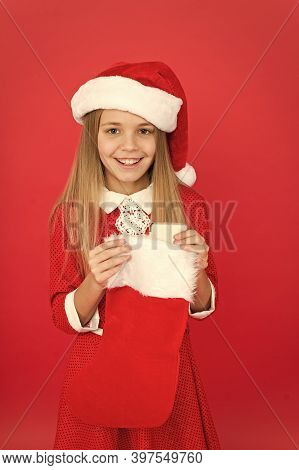 Christmas Celebration Ideas. Child Santa Claus Costume Hold Stocking. Happy Smiling Face. Emotional